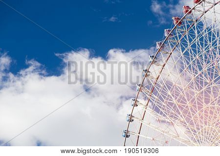 Path of Giant funfair ferris wheel against blue sky background