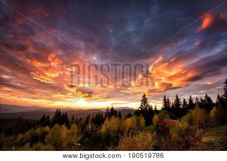 dramatic sundawn in the mountain autumn landscape with colorful forest