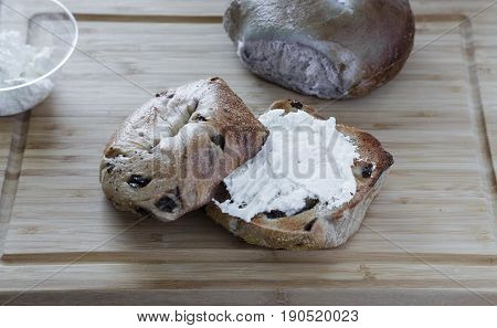 Cream Cheese on a Raisin Bagel with Blueberry Bagel in background