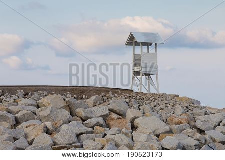 Wooden White lifeguard over rock coastline and blue sky background