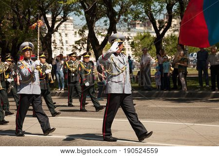 Khabarovsk Russia - May 28 2017: Brass orchestra marching performance. Asian musicians in uniform playing wind instruments on parade. IV international military music festival