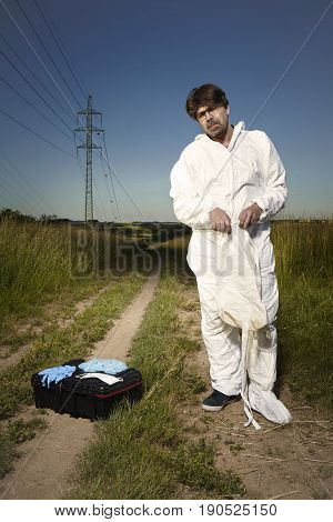 Criminologist technician wearing disposable overall and protective equipment
