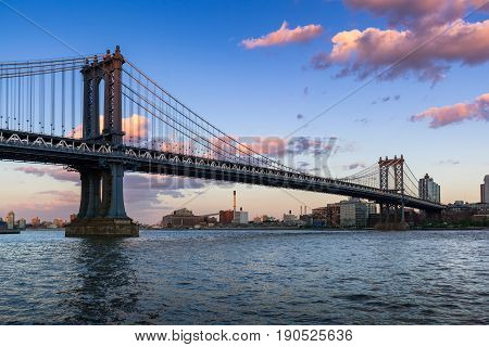 Manhattan Bridge (long-span suspension bridge) over the East River at sunset with view of Brooklyn. New York City