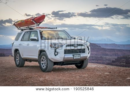 POTASH , UT, USA - MAY 7, 2017:  Toyota 4runner SUV (2016 trail edition) with a whitewater kayak on roof racks in the Colorado RIver canyoin near Moab.