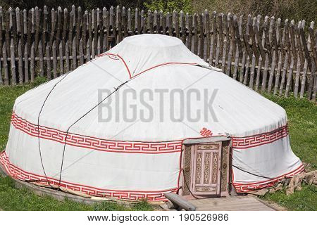 ancient medieval round marching white military textile tent in a fortification construction with fence from wooden logs