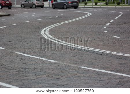 curved road made from a cobblestone stone blocks with marking in historical city centre