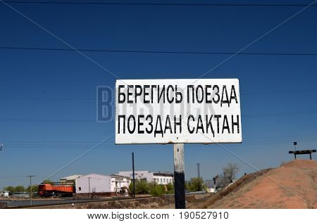 Road sign-Beware of train (KZ and RU).Area of former Soviet  anti-ballistic missile testing range.Kazakhstan.May 6, 2017.Sary Shagan.Kazakhstan