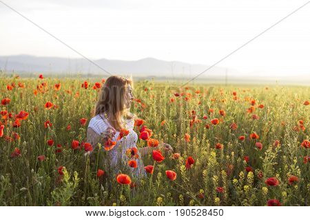 Woman in white dress standing in a full field of poppies