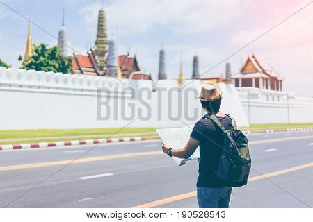 Young man traveler with backpack and hat looking the map with Grand palace and Wat phra keaw at Bangkok Thailand. Traveling in Bangkok Thailand