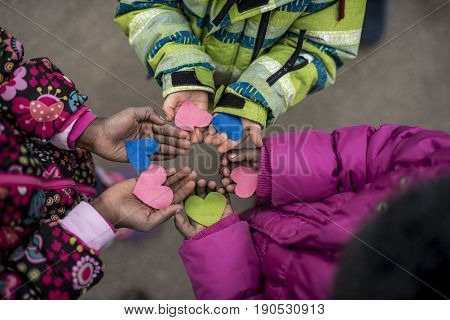 Children holding hearts cut of colored paper in their hands standing in circle symbolising love and friendship view from above.