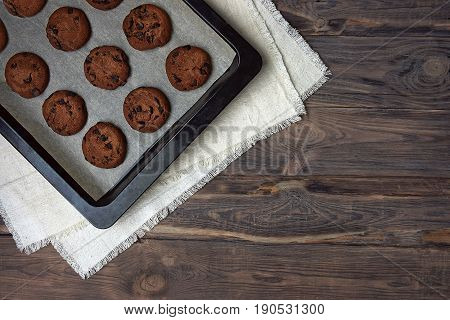 Homemade chocolate chip cookies on a baking sheet. top view. The selected focus. Baking on an old wooden background. Rustic style.