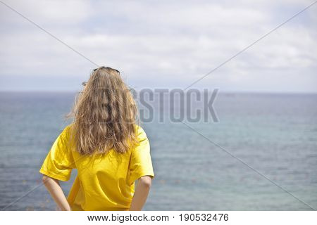 Blonde woman wearing a yellow t-shirt observing the blue sea in a sunny day
