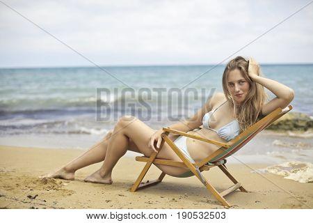Young woman wearing bikini sitting in a beach chair at the beach