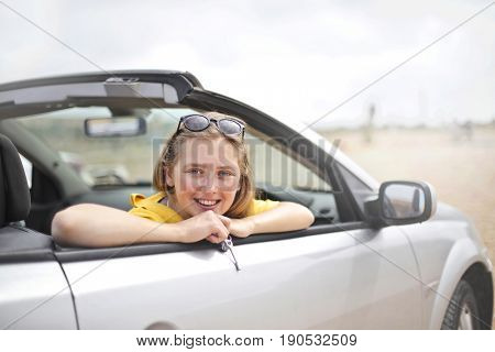 Girl enjoying a vacation travelling on a convertible car