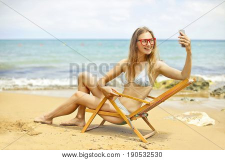 Pretty girl sitting in a beach chair doing a selfie at the seaside