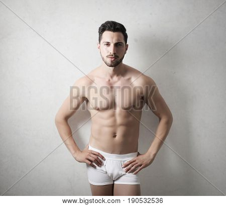Handsome young man showing his fit and muscular body