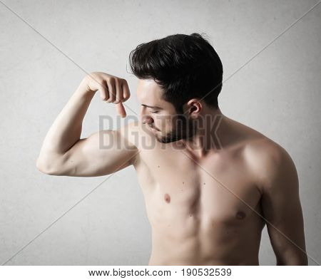 Muscular man with naked chest checking his strength