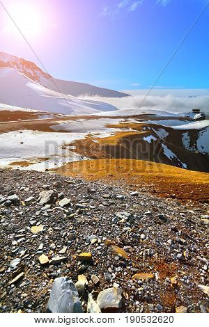 Snow-capped mountains with melting snow and orange grass. Sunrise. Clouds at the top of the glacier in the background.