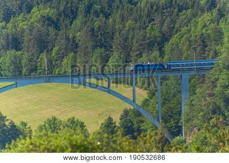 Personal train on a distant bridge over the valley. The railway bridge in the Czech Republic in the village of Dolni Loucky