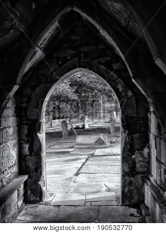 porch in the medival church in heptonstall looking out on to graveyard with arches and old stonework