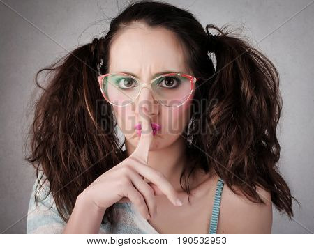 Girl with pigtails and vintage glasses asking for silence