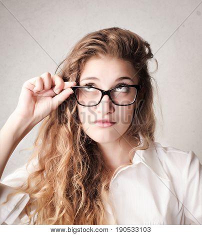 Doubtful girl wearing glasses looking upwards