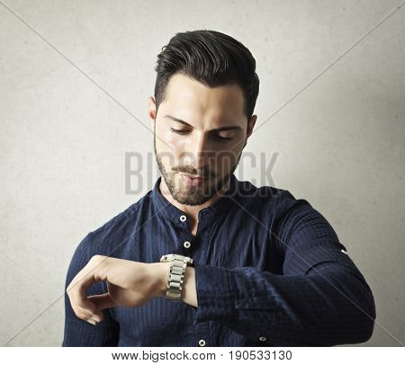 Handsome young businessman checking the time