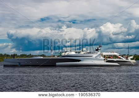 Large silver trimaran. Luxury yacht sailing by the river in Riga