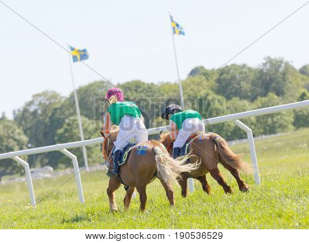 STOCKHOLM SWEDEN - JUNE 06 2017: Rear view of two young girls riding pony gallop race horses at Nationaldags Galoppen at Gardet. June 6 2017 in Stockholm Sweden