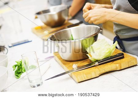 Education in the culinary school. The process of cooking and slicing vegetables by students. Girls cut vegetables for vegetarian dishes. Soft focus and beautiful bokeh.