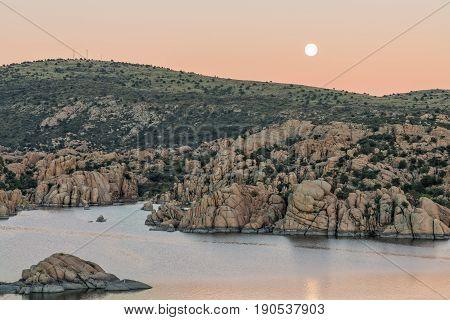 a full moon rising at sunset over Watson lake Prescott Arizona