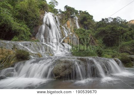 Beautiful cascading water of La Conchuda waterfall in Rio la Venta Canyon in Chiapas Mexico surrounded by lush green vegetation on cloudy day