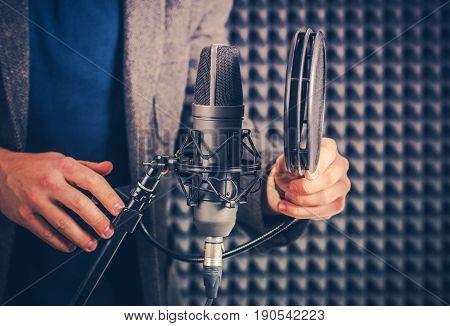 Male Voice Talent in the Studio Preparing Audio Recording Equipment For the Next Recording Session.