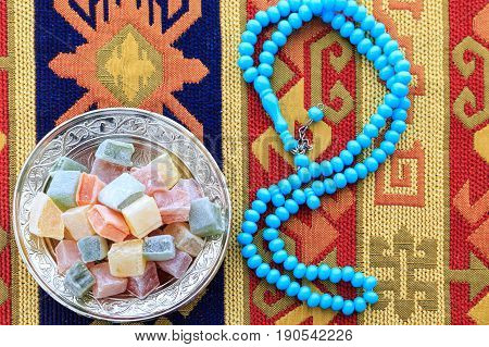 Turkish delights and blue rosary on traditional turkish carpet poster