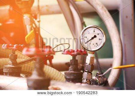 Pressure gauge with retro picture style. Worker or Operator monitoring oil and gas process by the gauge for routine record and analysis oil and gas production process.