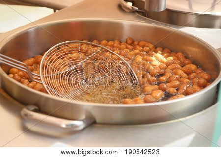Sweet mini donuts frying in oil. Pot with mini donuts and colander.