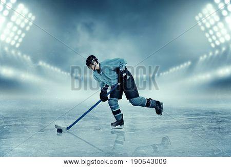 Ice hockey player in equipment poses on stadium