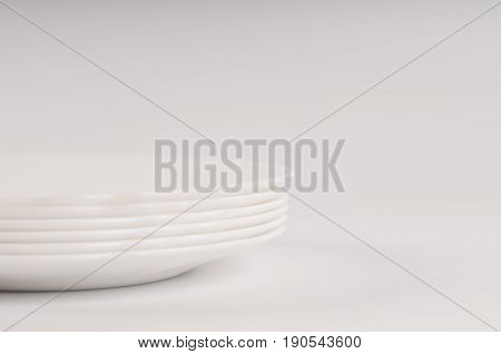 Set of white plane dishes on white background in a pile