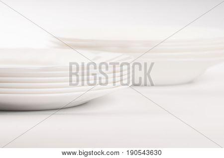 Two piles of white plane dishes on white background six in each