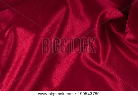 Red silky textile background with waves and glare