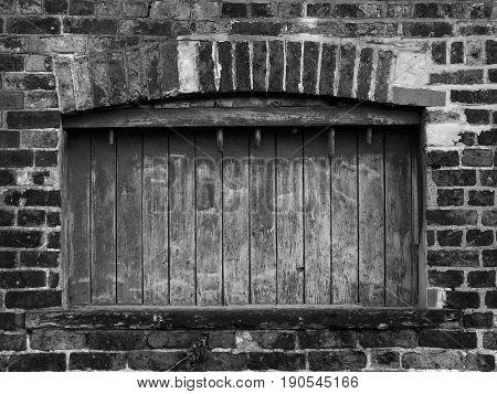 dark boarded up window in old derelict building