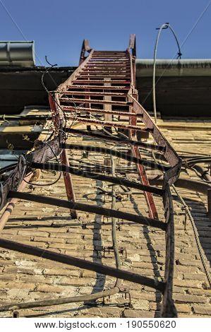 Damaged, deformed metal ladder on the side of an old industrial building