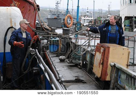 Murmansk, Russia - May 25, 2010: Two men moored ship at a pier