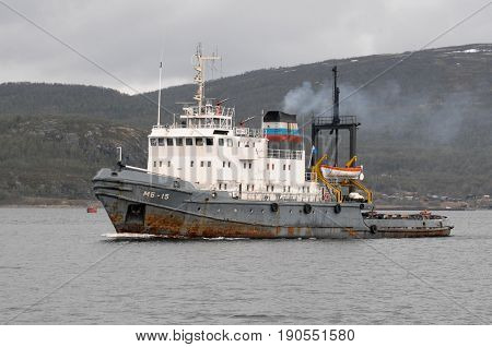 Murmansk, Russia - May 25, 2010: The marine tugboat sails along the Kola Bay water area