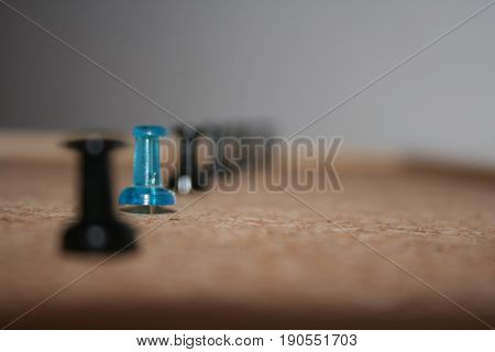 One blue pin among black ones in the cork-board