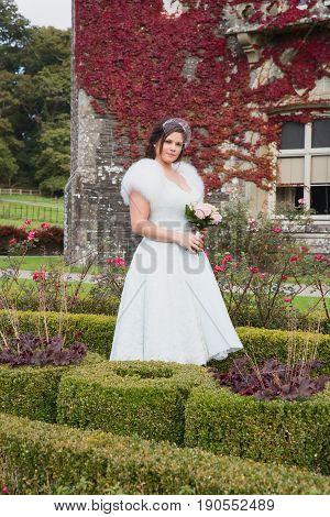 Bride Has Photos Taken In Formal Garden During Autumn