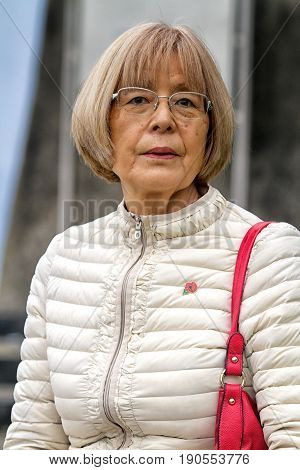 Old Japanese Woman With Red Shoulder Bag And Glasses Looks At Camera