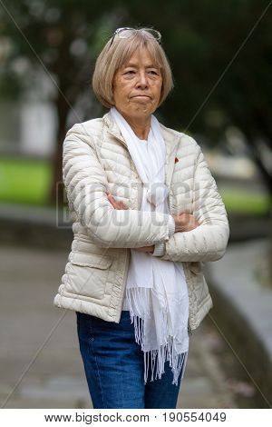 Older Lady Stands With Her Arms Crossed