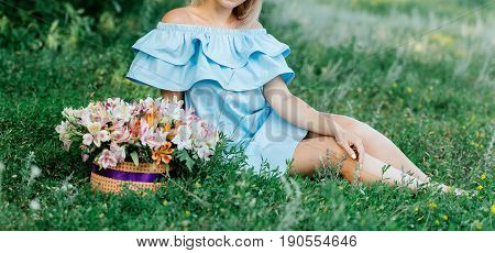 Beautiful Young Smiling Girl In Blue Dress With Open Shoulders Sitting On Green Grass Next To Bouque