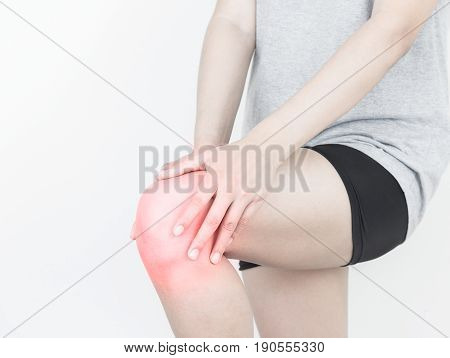Young woman with hands holding knee pain isolated on white background.